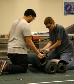 Students rolling up the rugs