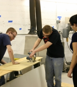 Alumni helping students use the circular saw